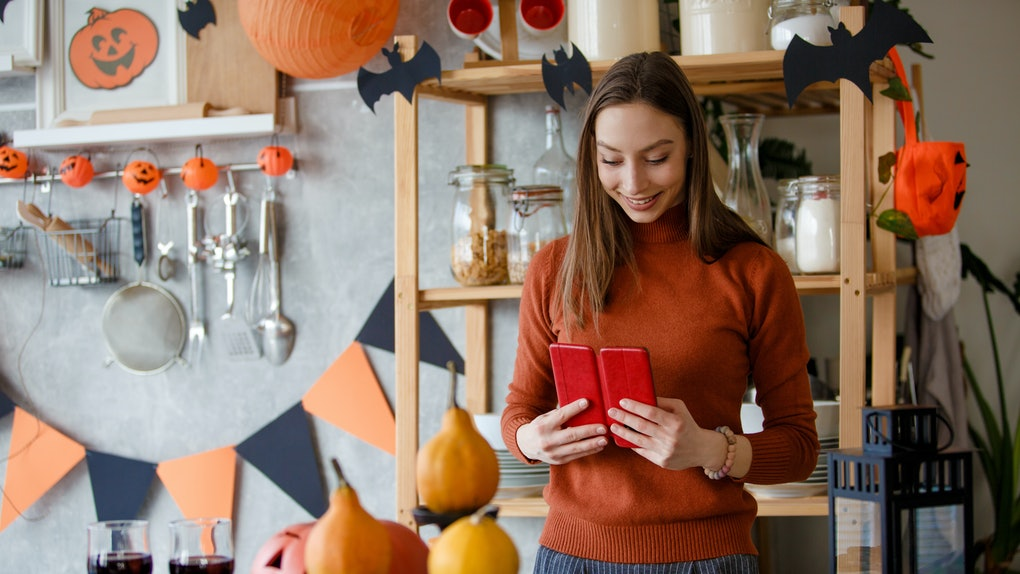 A young woman stands with her phone next to Halloween decorations and cookies set up in her kitchen.