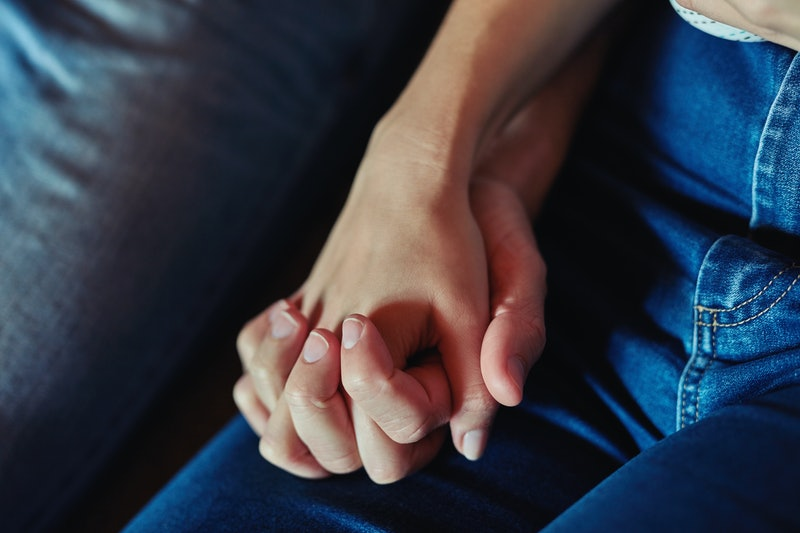 A woman holds her partner's hand following a pregnancy loss. Women explain what their miscarriages were like, and what they want you to know.