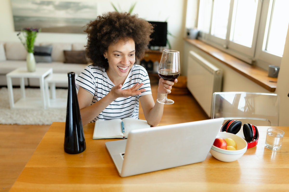 A young Black woman laughs while video chatting on her laptop and drinking a glass of red wine.