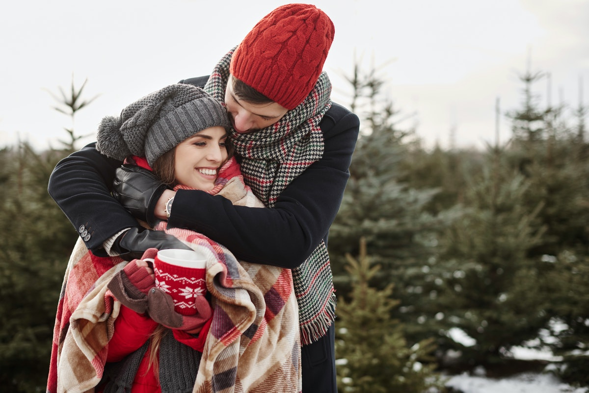 A couple wrapped up in a holiday blanket, embrace outside with a mug of coffee.