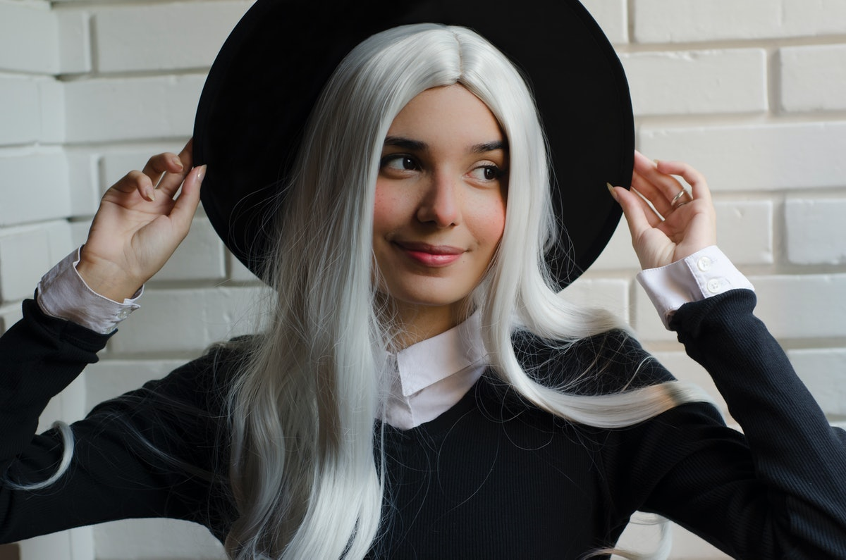 A woman with a long white wig poses in her witch hat for Halloween.