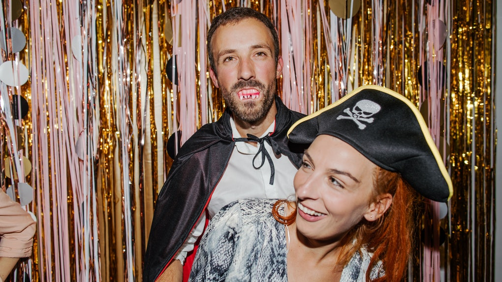 A young couple laughs while wearing Halloween costumes and standing in front of pink and gold streamers.