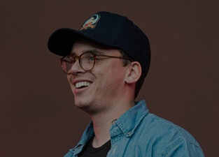 Logic the rapper can be seen in a hat, smiling at his audience.