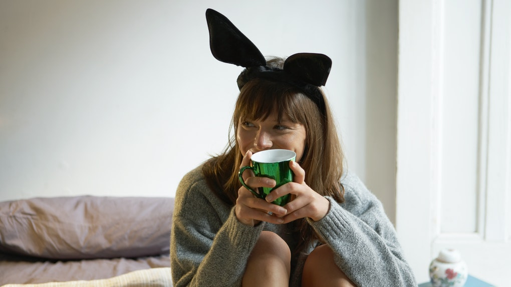 A woman in a gray sweater holds a green mug of coffee while wearing bunny ears.