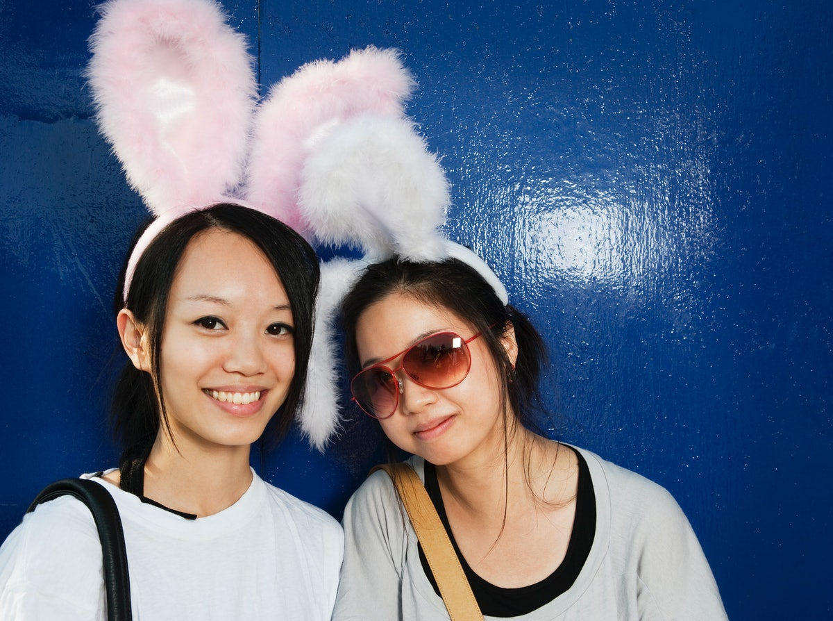 Two happy friends smile while wearing pink bunny ears and standing in front of a dark blue wall.