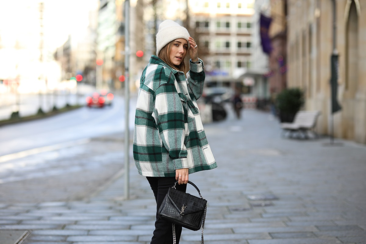 A young woman in a flannel-printed shacket walks down a city street.