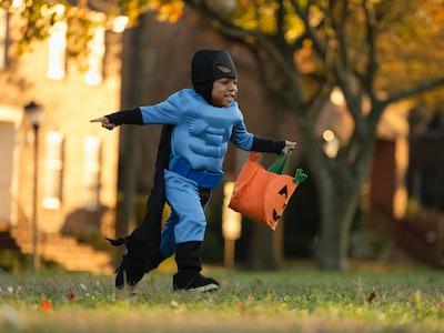 little boy running with a halloween bag