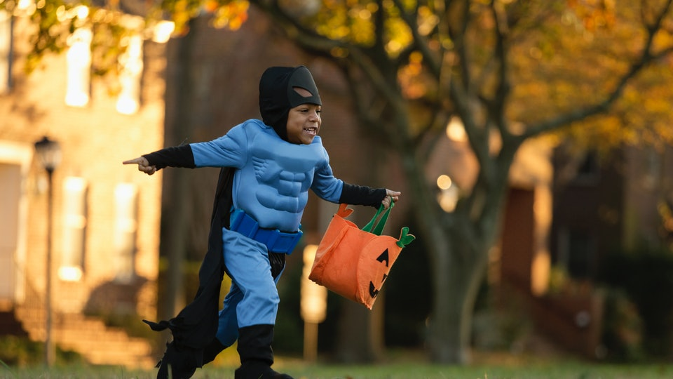 little boy running with a halloween bag