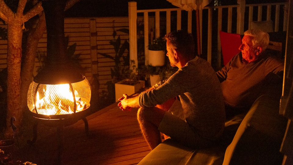 two men sitting outside in front of outdoor heater