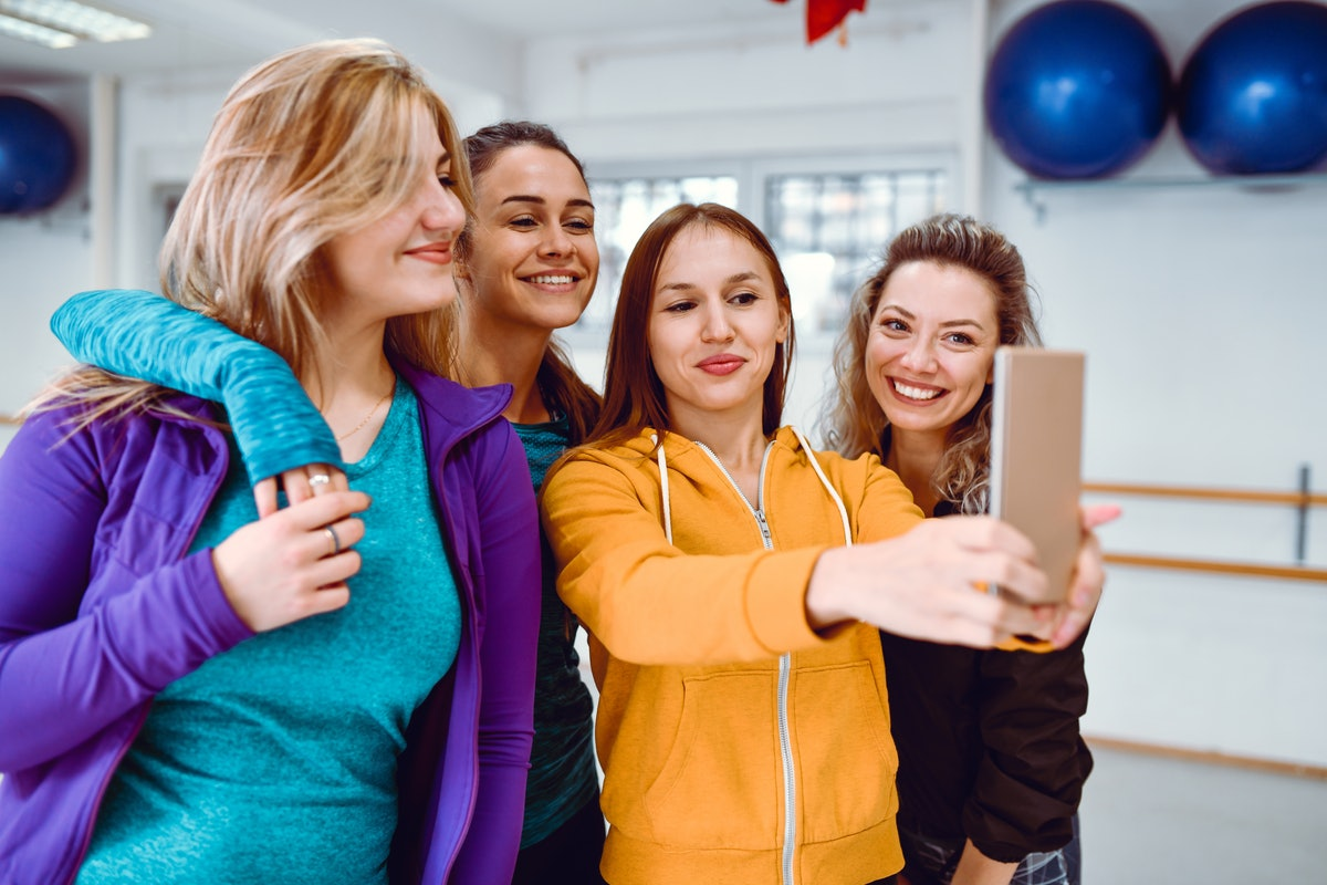 A group of women take a selfie on their phone while wearing brightly-colored sweatshirts.