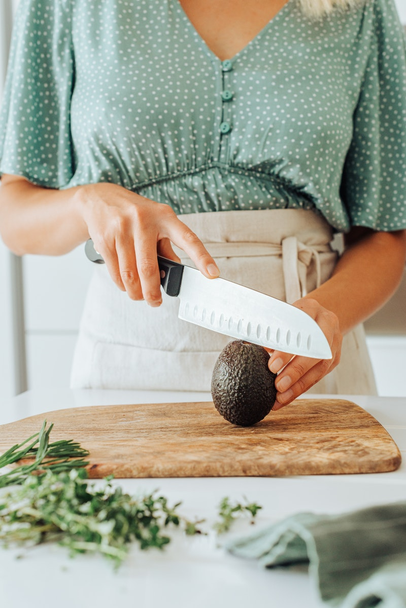 A woman slices an avocado on a wooden cutting board. Nutritionists explain foods that can balance out your hormones.