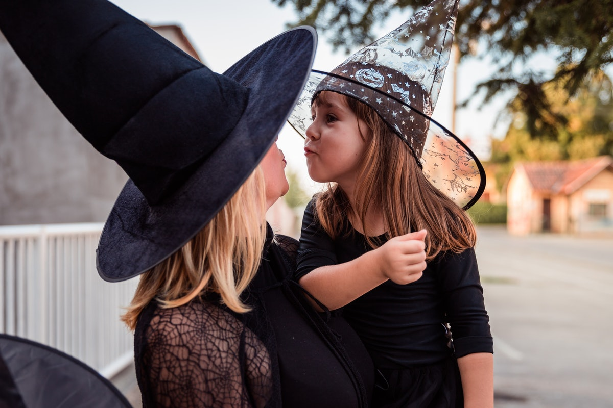 A blonde woman dressed like a witch on Halloween kneels down while her niece who's also dressed like a witch makes a kissy face.