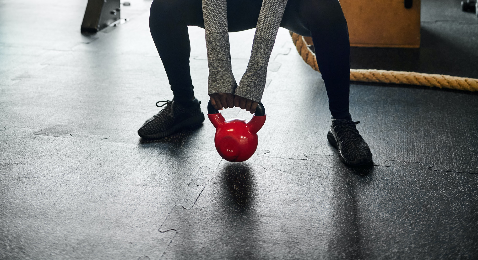A person wearing a mask performs a sumo kettlebell squat in the gym. Your back-to-gym workouts don't have to be complicated to be effective.