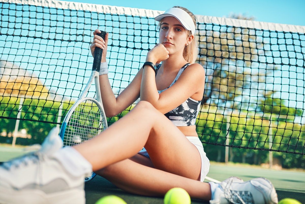 A woman wearing a tennis outfit, sits on the court with her racket and some balls.