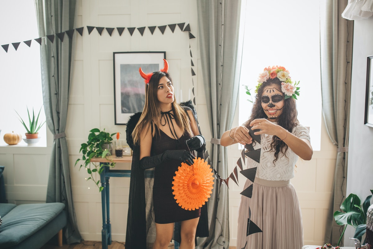 Two women hang up Halloween decorations in their home.