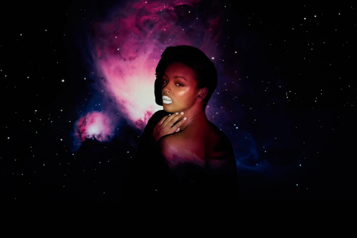 A woman with white lipstick poses in front of a night sky backdrop.
