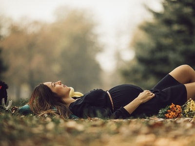 pregnant woman lying on her back in the grass in fall