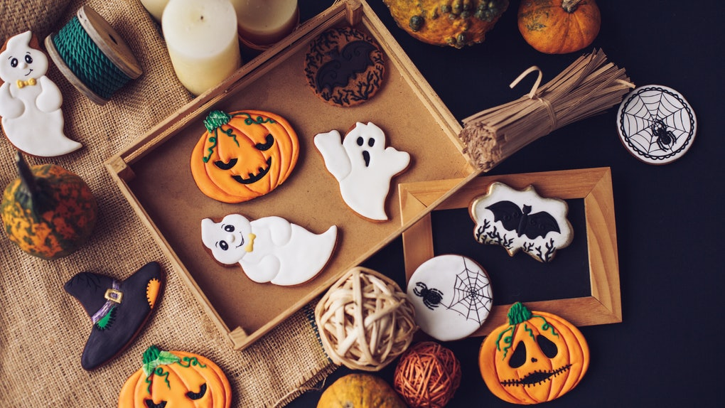 Decorated pumpkin spice cookies sit on a tray surrounded by fall decor.
