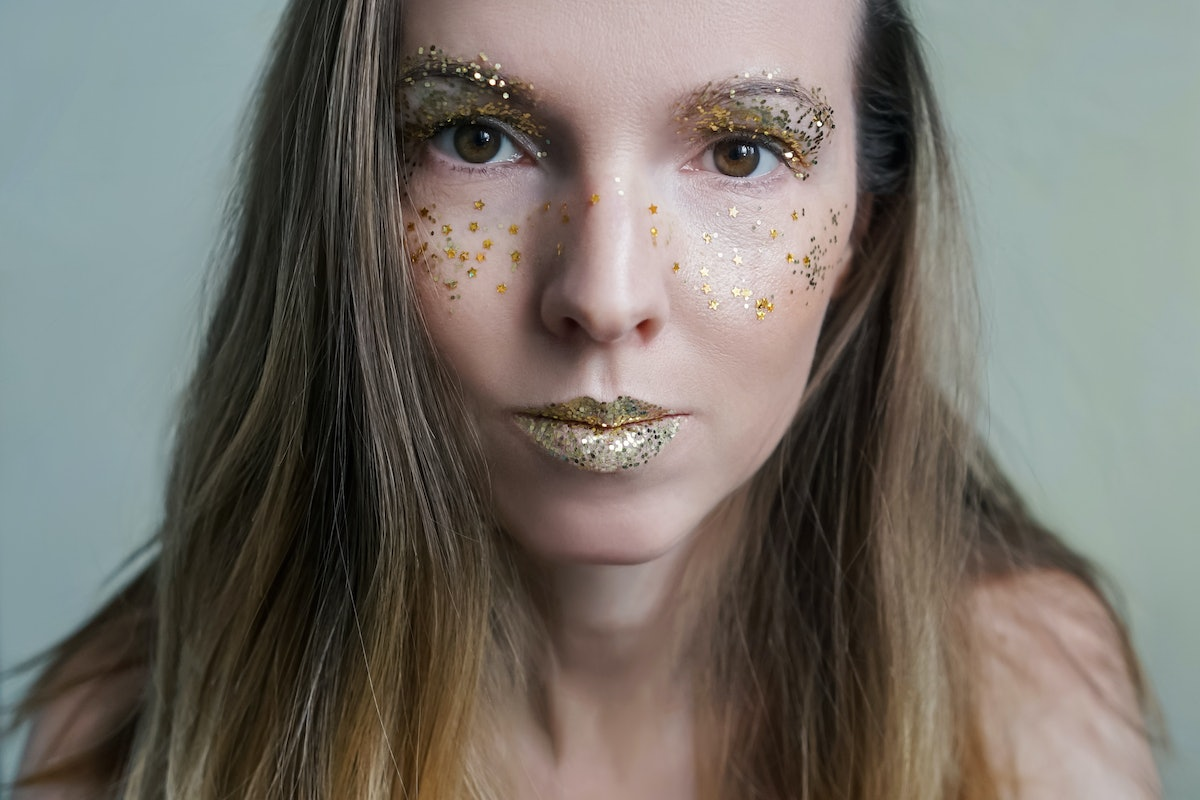 A blonde woman has glittery eye shadow and lipstick on.
