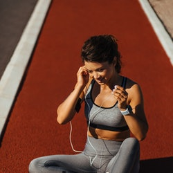 A woman with a fast metabolism sits on a running track with a blue water bottle. Doctors explain physical signs of having a fast metabolism.