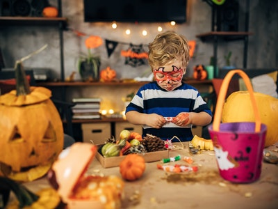 little boy unwrapping halloween candy