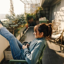 A woman puts her feet up while drinking coffee on a screened in porch. Here are breast cancer stats everyone should know.