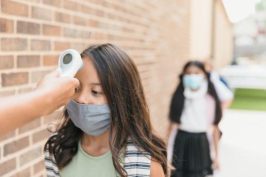 little girl getting her temperature taken at school