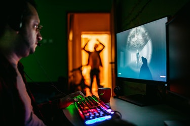 A man playing video games while someone in silhouette tries to get his attention.