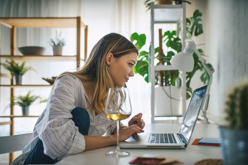 A woman talks to strangers online on a computer while drinking a glass of white wine. Therapists say talking to strangers online can have therapeutic benefits.