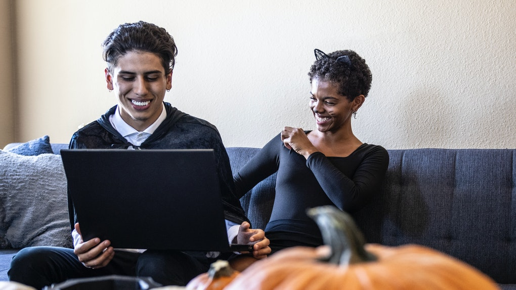 A young couple laughs while dressed up in Halloween costumes and having a virtual experience via their laptop.