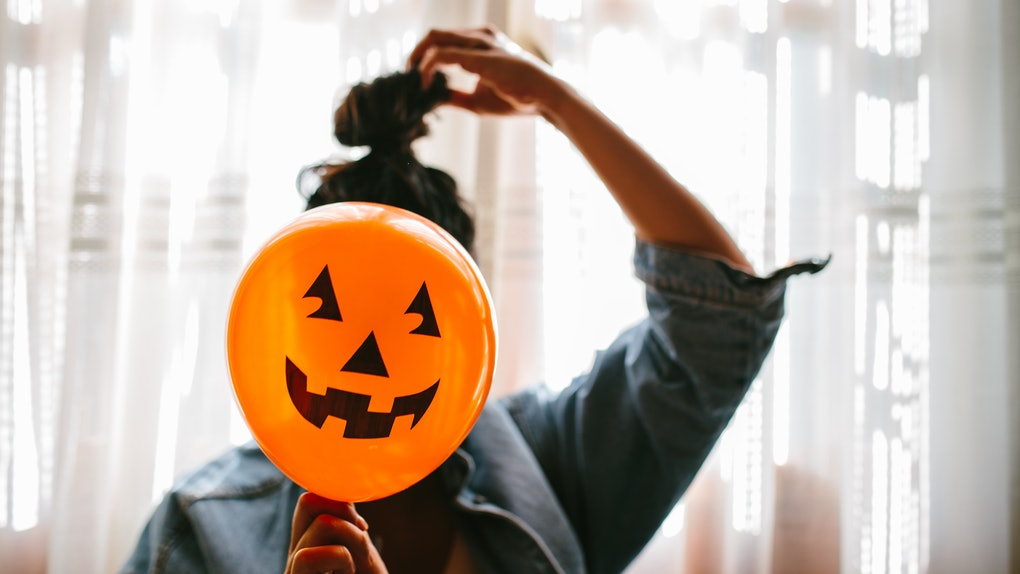 A young woman holds a pumpkin balloon in front of her face on Halloween.