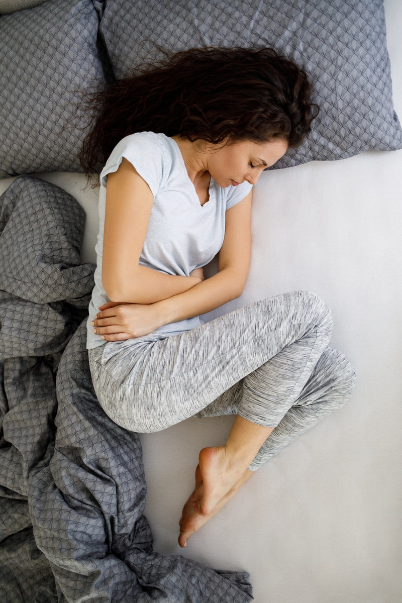 A woman holds her stomach while lying in bed. Doctors explain what it could mean if you test negative for a UTI but still have symptoms.