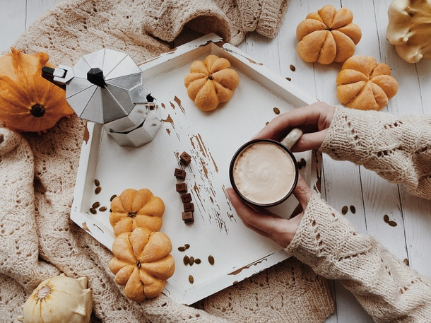 A woman sets down a cup of pumpkin spice coffee on a tray filled with mini pumpkins.