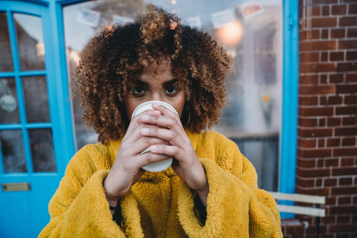 A woman in a yellow sweater enjoys a cup of coffee outside.
