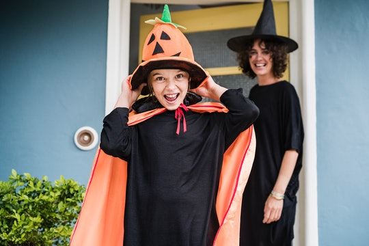 mom and daughter in witch costumes leaving house