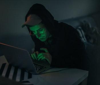 Hooded man sitting at his computer.
