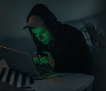 Hooded man sitting at his computer.