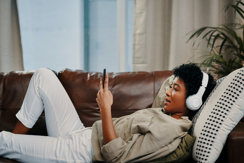 A woman with headphones on selects a binaural beats playlist for migraine. A doctor explains why binaural beats can't cure migraines.