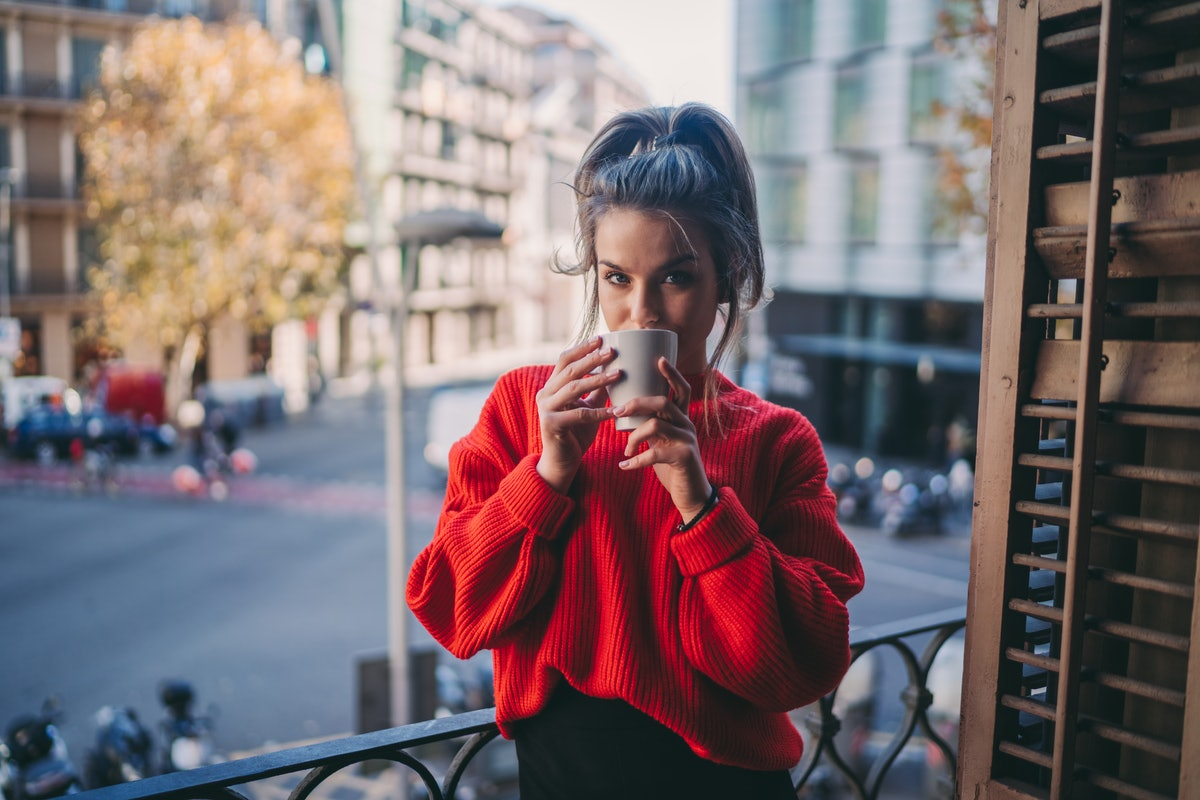 A woman enjoys a cup of coffee on her balcony in the fall.