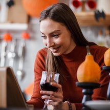 A woman looks at a tablet on a stand. she's surrounded by pumpkins and bats and other spooky halloween decor