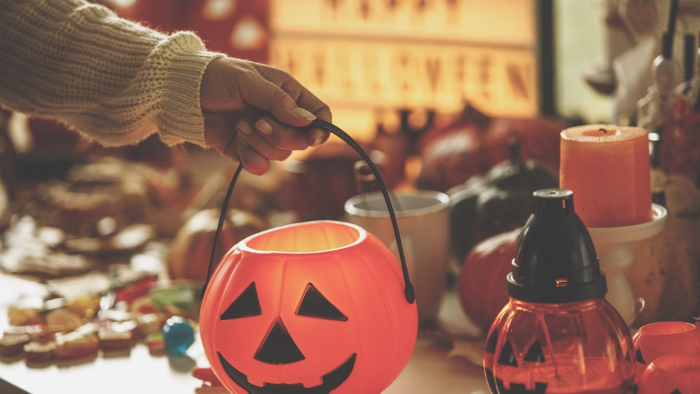 A young woman holds the handle of a pumpkin bucket surrounded by Halloween decor and goodies.