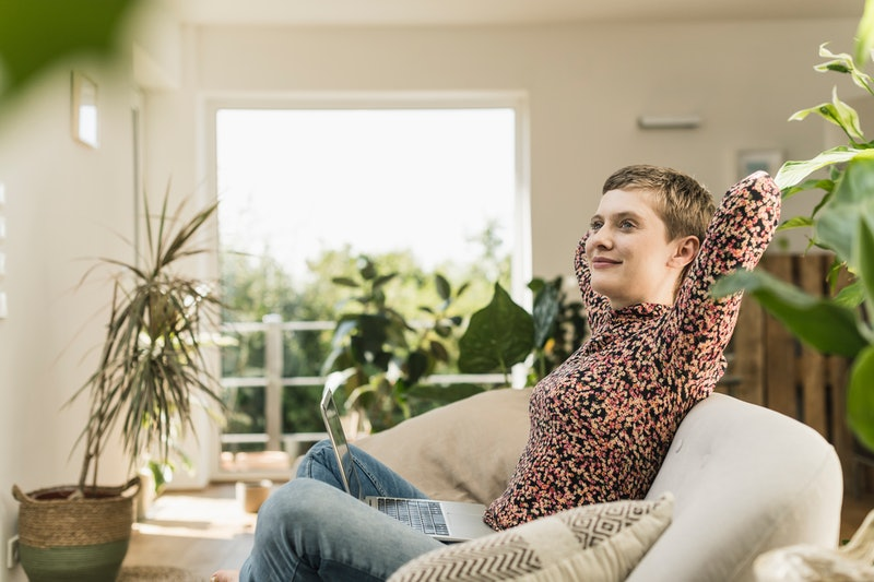 A woman with short hair sits on a white couch surrounded by plants. This article details 7 signs of high functioning ADHD in adults.