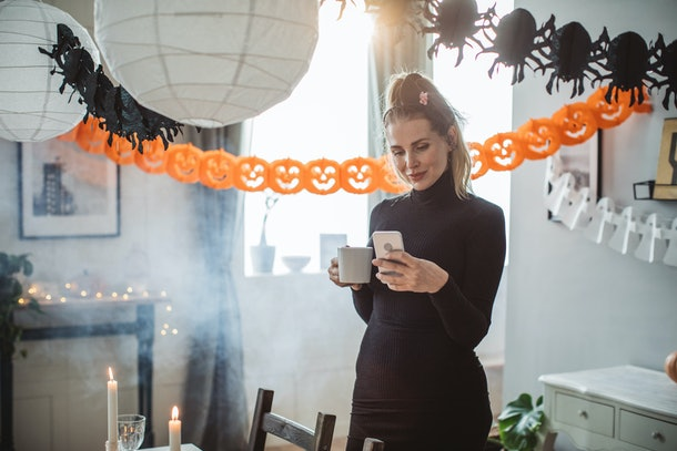 A woman in a black dress holds a cup of coffee and texts while standing in a living room that's decorated for Halloween.
