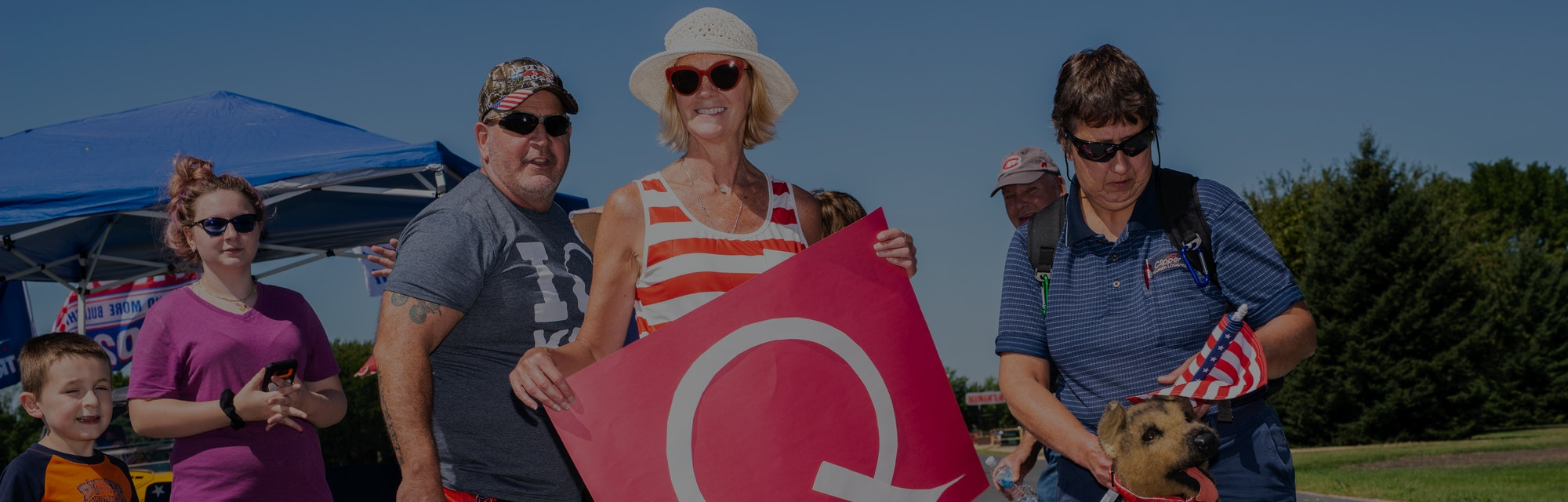 A QAnon supporter can be seen holding a Q for the movement.