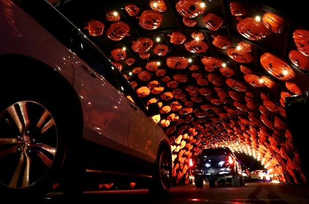 Cars stop in a pumpkin tunnel of a Halloween drive-thru event.
