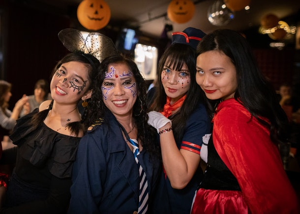 A group of women in Halloween costumes stand under hanging pumpkins.