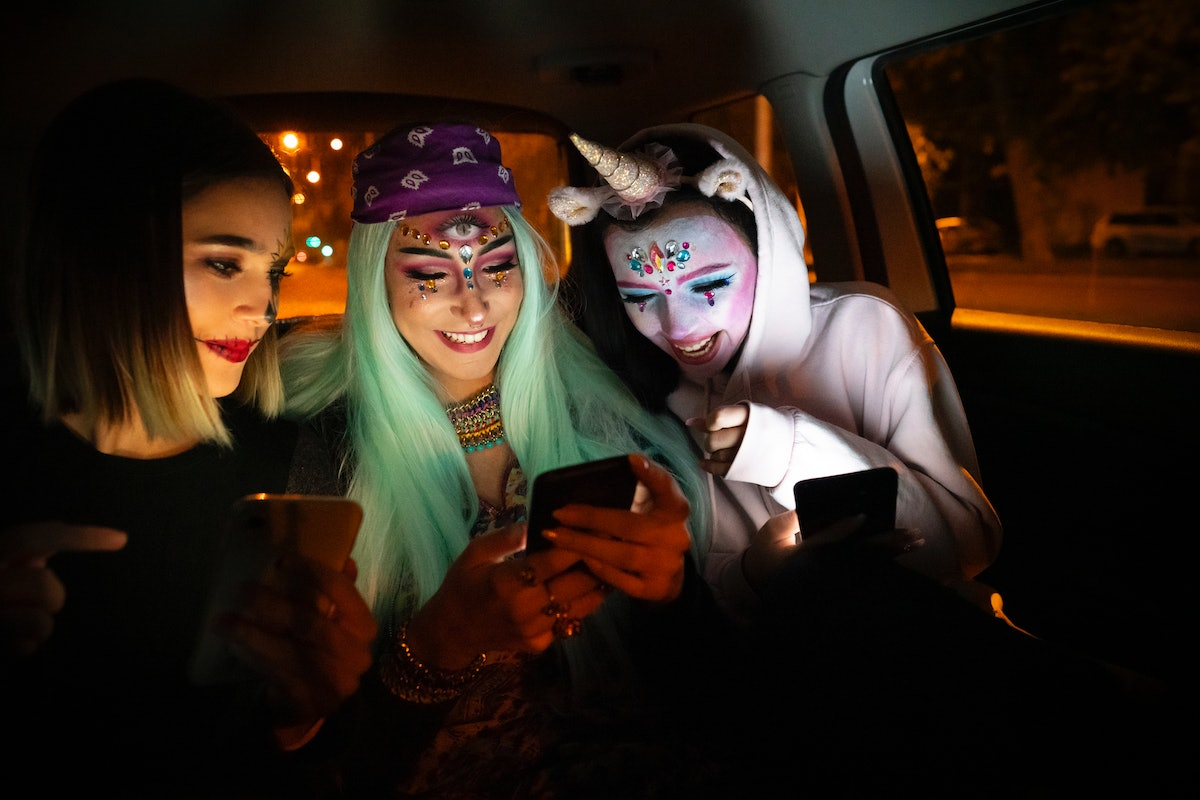 Three friends dressed up for Halloween sit in the backseat of a car while looking at one of their ce...