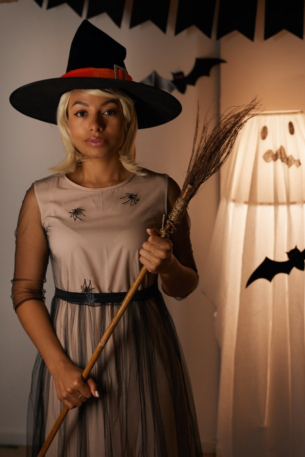 A young Black woman dressed up like a witch poses for a picture in her home.