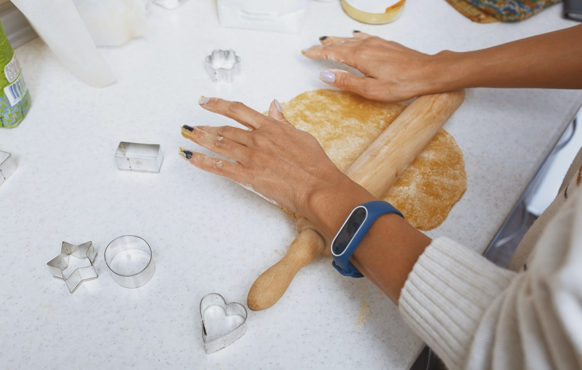 A young woman rolls out sugar cookie dough on a counter with a rolling pin.