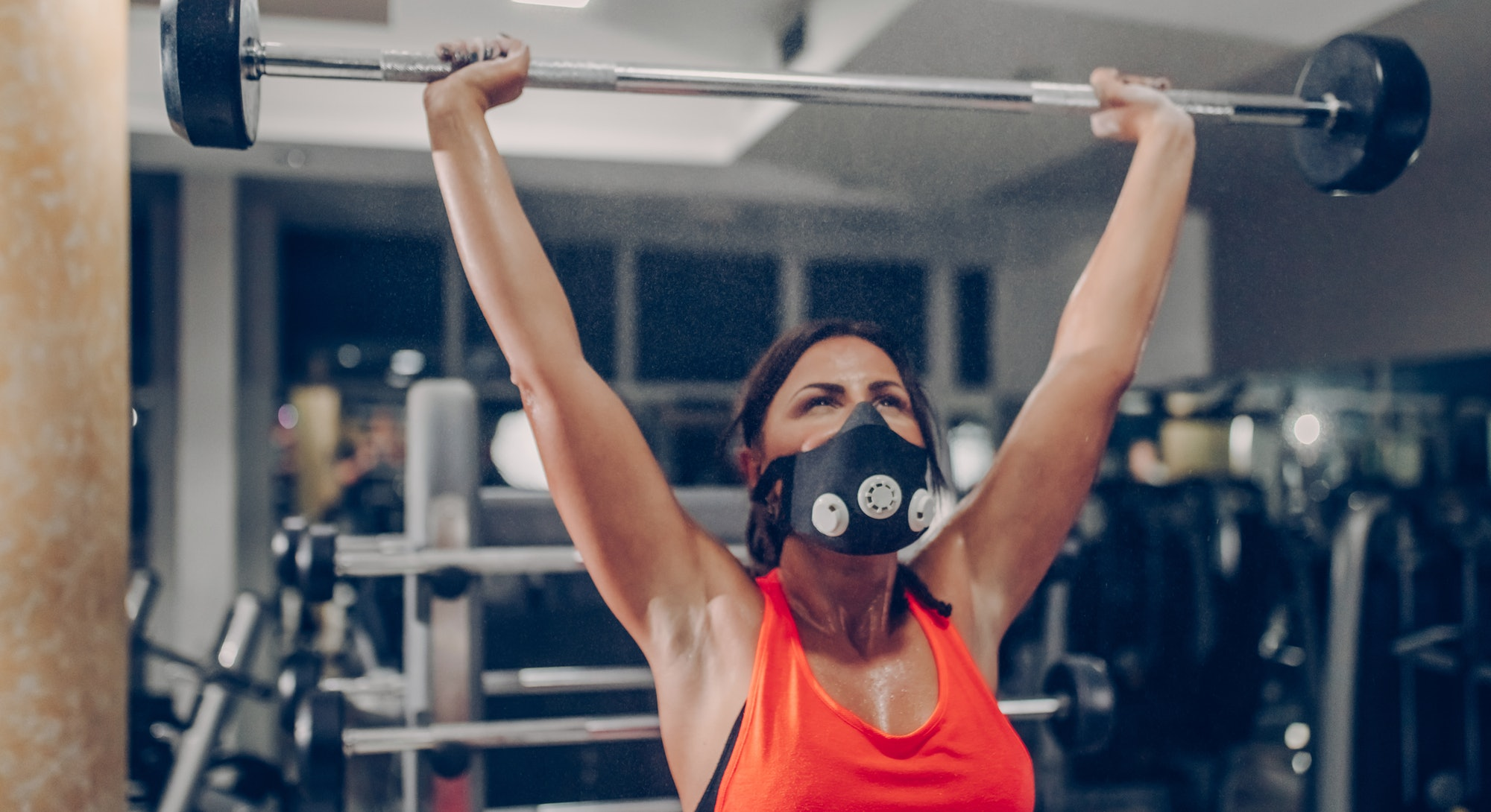 A person wearing an orange tank top and a black mask presses a barbell overhead. Resistance training has a wealth of health benefits.
